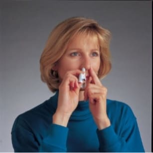 Keep your head upright and close your mouth. While gently taking a breath in through your nose, press the blue plunger firmly to release the dose of Imitrex nasal spray. image