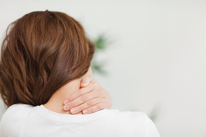 Woman in pain with hand on neck