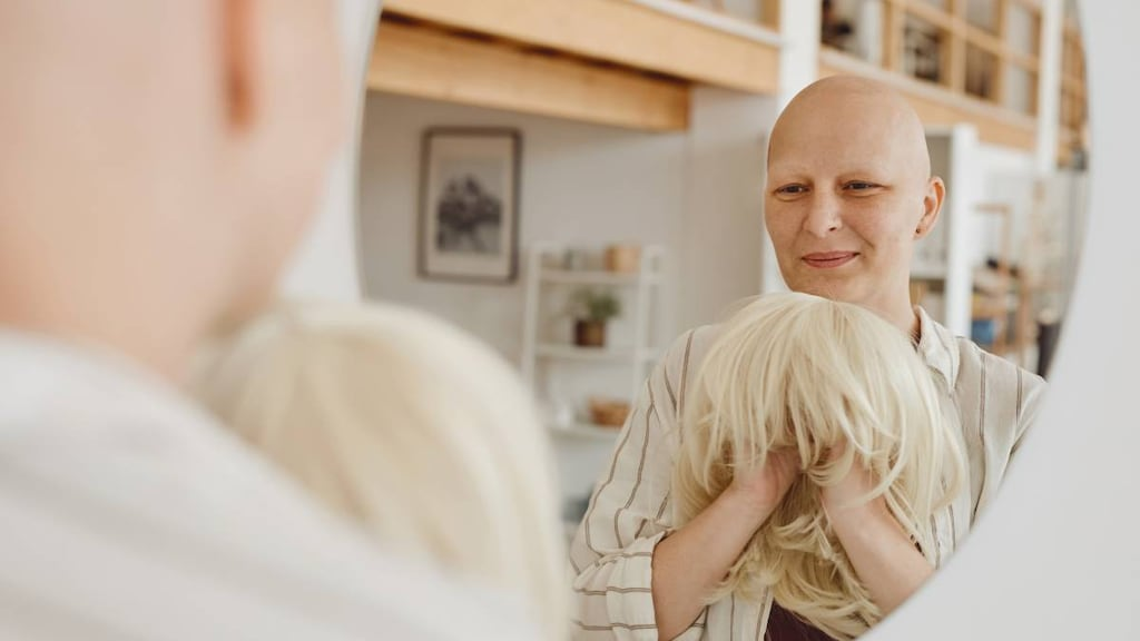 Chemotherapy patient with hair loss putting on a wig.
