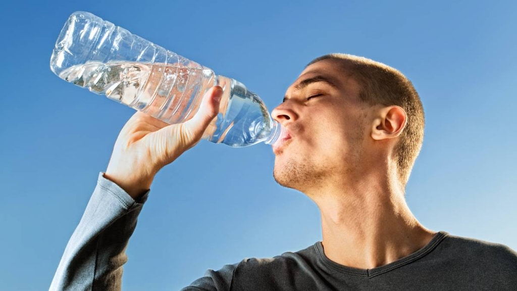 Man drinking water from a bottle.