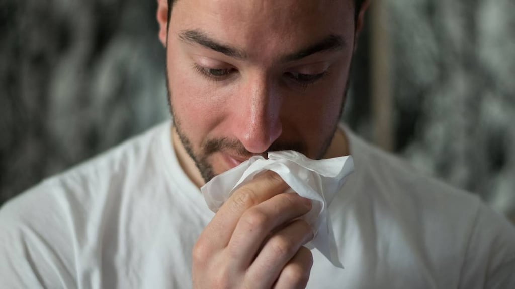 Man wiping nose with tissue