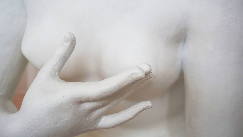 Sculpture showing breast being checked