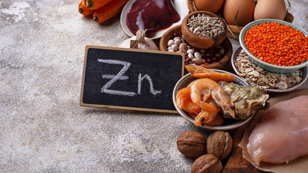 zinc chalkboard sign with prawns, oyster, eggs and vegetables around it.image