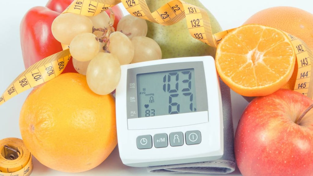 Blood pressure monitor with result of measurement, fresh fruits with vegetables and tape measure.ima