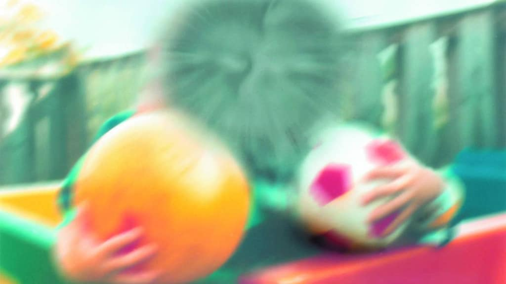 Blurred image of child holding balls