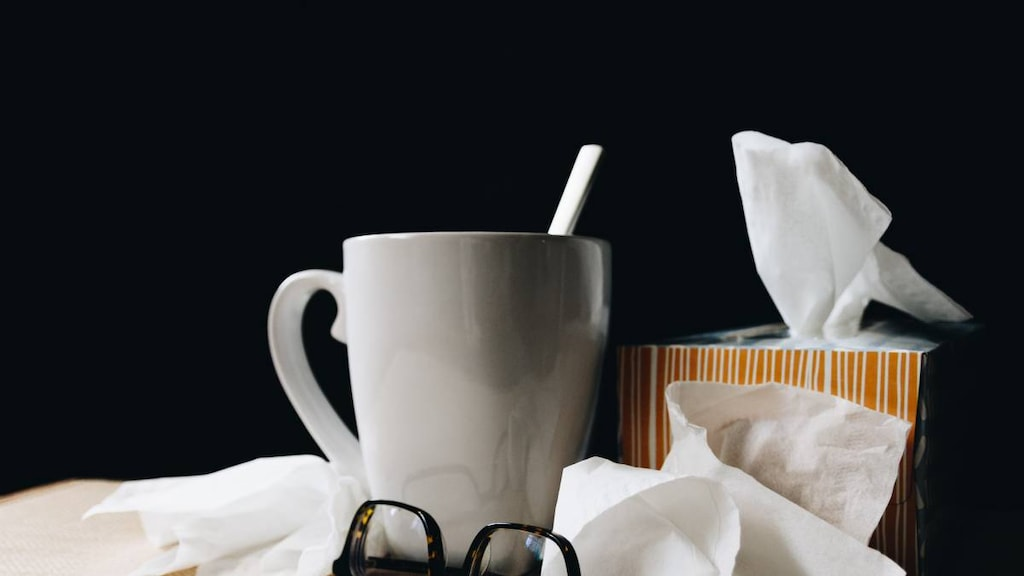 Tissues, mug and reading glasses collected during illness