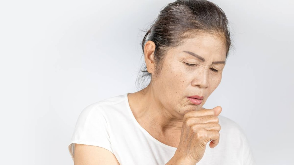 An older woman coughing