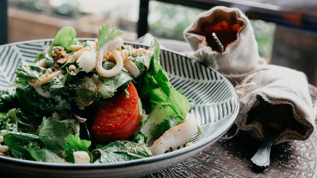 A bowl of salad and seafood sitting on a table with cutlery wrapped in a napkin.