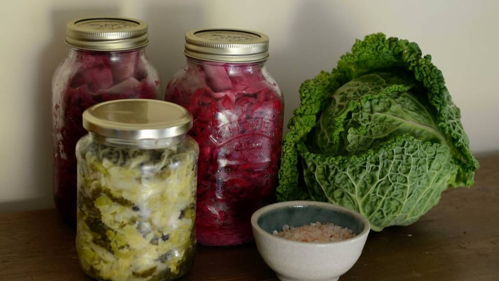 Three jars of fermented food, a cabbage and a small dish on a bench.