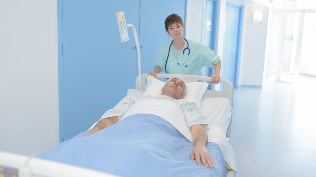 Man in hospital bed being moved